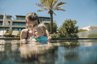 Happy mother and baby son in swimming pool - MFF04271