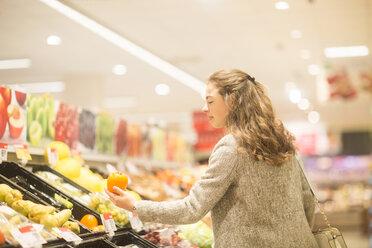 Young woman choosing kaki in supermarket - SGF02124
