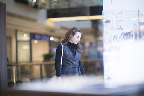 Young woman looking at showcase in a shopping mall - SGF02130
