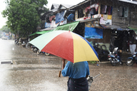 Myanmar, back view of man under umbrella in the rain - IGGF00251