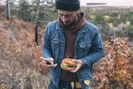 Man with burger and smartphone - VPIF00294
