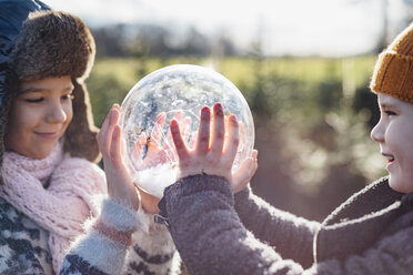 Brother and sister looking into crystal ball filled with snow, making a wish - MJF02211