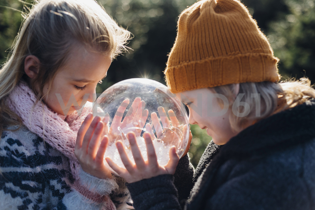 Brother and sister looking into crystal ball filled with snow, making a wish - MJF02214 - Jana Mänz/Westend61