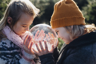 Brother and sister looking into crystal ball filled with snow, making a wish - MJF02214