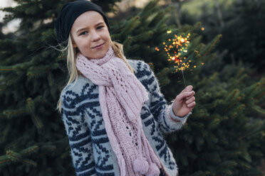 Girl holding sparkler in front of fir trees - MJF02226
