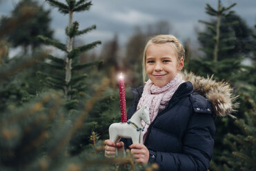 Little girl standing in front of fir trees with a burning candle - MJF02229