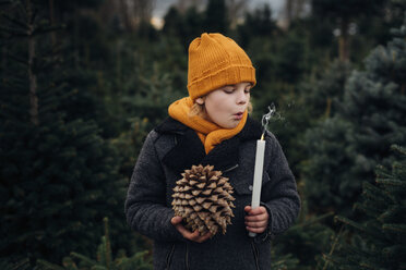 Little boy standing in front of fir trees blowing out candle, holding pine cone - MJF02232