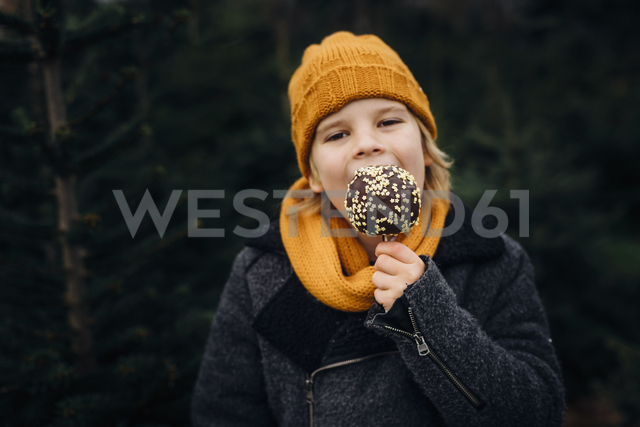 Little boy standing in front of fir trees, eating chocolate dipped apple - MJF02241 - Jana Mänz/Westend61