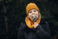 Little boy standing in front of fir trees, eating chocolate dipped apple - MJF02241