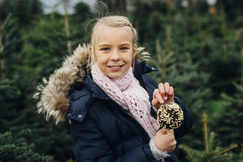 Little girl standing in front of fir trees holding chocolate dipped apple - MJF02244