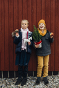 Girl and laughing boy standing in front of wooden wall with toy horse and chocolate dipped apple - MJF02250