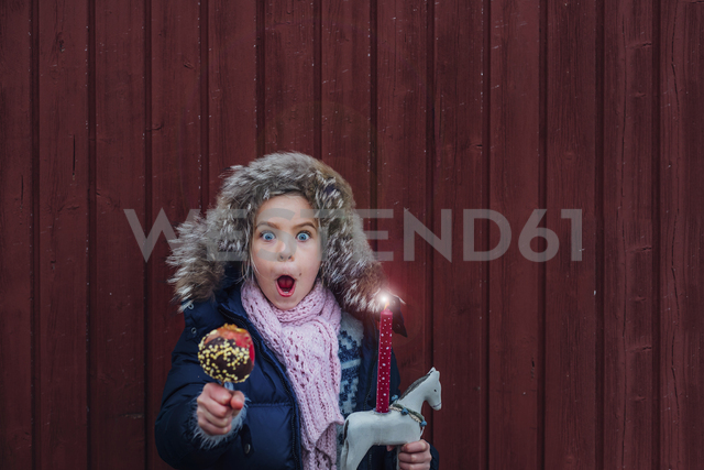 Girl standing in front of wooden wall with toy horse and chocolate dipped apple, looking amazed - MJF02253