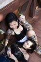 Tattooed lesbian couple laughing and having fun on wooden bridge - IGGF00255