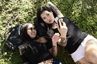 Tattooed female friends listening to music lying on the grass - IGGF00258