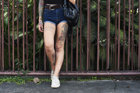 Legs of tattooed woman standing at garden fence - IGGF00261