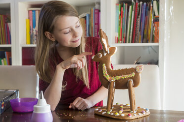 Smiling girl with homemade gingerbread reindeer at home - SARF03448