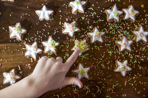 Girl's hand touching cinnamon star - SARF03451