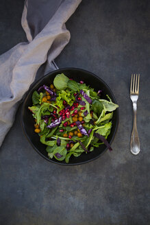 Bowl of mixed leaf salad with pomegranate seed, red cabbage and roasted curcuma chick peas - LVF06517