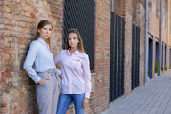 Two serious businesswomen outside brick building - VABF01415