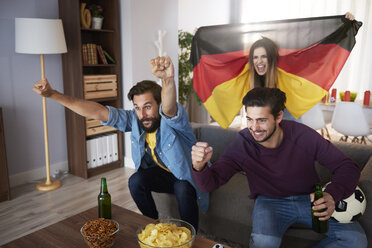 Excited German football fans watching Tv and cheering - ABIF00070