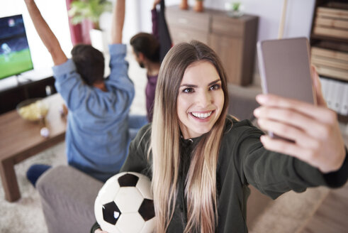 Female soccer fan taking a selfie at home - ABIF00079