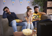 Disappointed friends sitting on the sofa watching Tv - ABIF00088