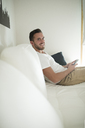 Smiling young man relaxing at home with his smartphone - RAEF01946