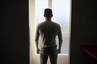 Man looking through window, rear view - RAEF01952