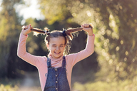 Portrait of laughing girl pulling her hair - XCF00165