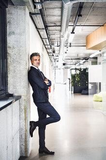 Portrait of confident mature businessman standing in office - HAPF02510