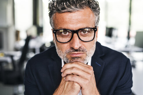Portrait of serious mature businessman wearing glasses in office - HAPF02528