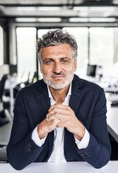 Portrait of confident mature businessman in office - HAPF02531