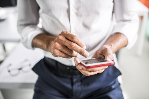 Close-up of businessman using cell phone in office - HAPF02537