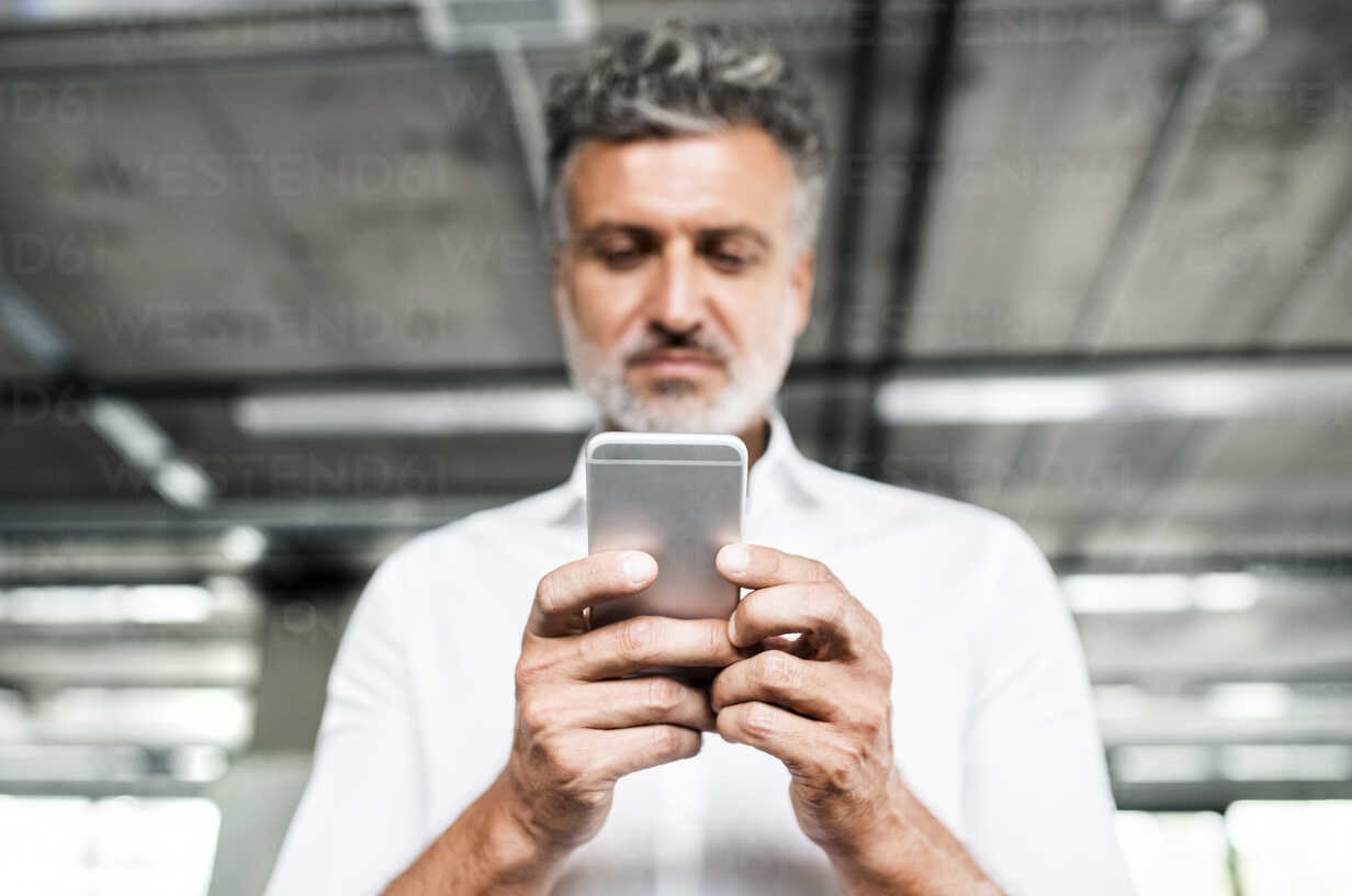 Low angle view of mature businessman holding cell phone - HAPF02543 - HalfPoint/Westend61