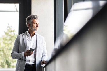 Mature businessman with cell phone looking out of window - HAPF02549