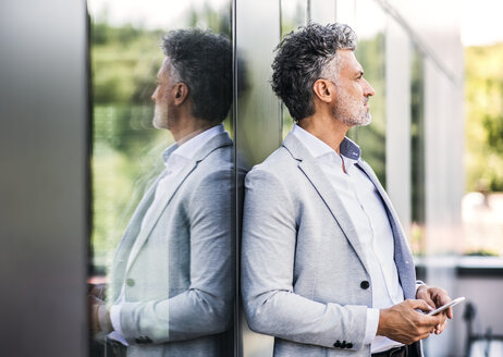 Mature businessman with cell phone at the window - HAPF02552