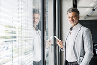 Portrait of smiling mature businessman at the window in office holding cell phone - HAPF02558