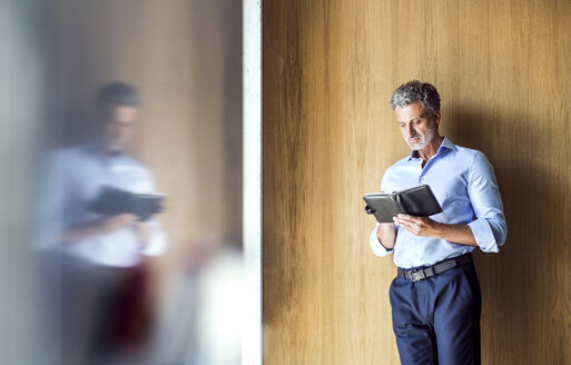 Reflection of mature businessman standing at wooden wall looking in diary - HAPF02570