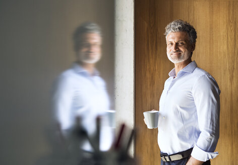 Portrait of smiling mature businessman holding coffee mug - HAPF02573