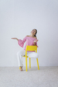 Portrait of laughing woman sitting on yellow chair - MOEF00428