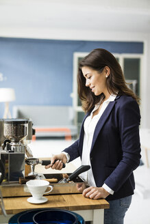 Smiling businesswoman preparing espresso with espresso machine in a loft - MOEF00431