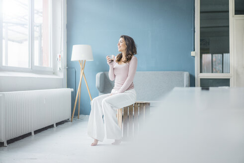 Young woman relaxing with glass of coffee in a loft looking out of window - MOEF00434