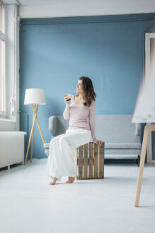Young woman relaxing with glass of coffee in a loft looking out of window - MOEF00437
