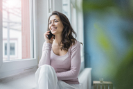 Portrait of young woman on the phone looking out of window - MOEF00443