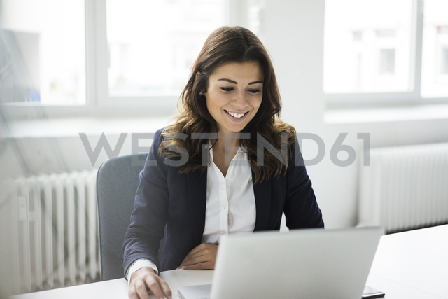 Portrait of smiling businesswoman sitting at desk in the office working on laptop - MOEF00452 - Robijn Page/Westend61