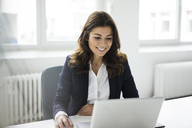 Portrait of smiling businesswoman sitting at desk in the office working on laptop - MOEF00452