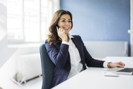 Portrait of smiling businesswoman on the phone sitting at desk in an office - MOEF00455
