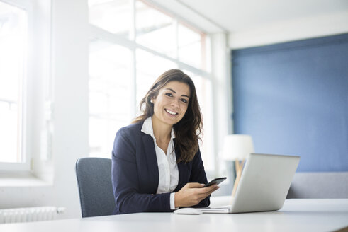 Portrait of happy businesswoman sitting at desk in the office - MOEF00458