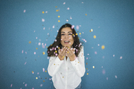 Portrait of laughing woman throwing confetti in the air - MOEF00473
