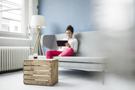 Smiling woman sitting on couch using tablet - MOEF00476
